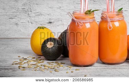 Macro picture of big mason jars with carrot smoothie on a gray wooden background. A few carrot tubes and zucchinis are in beautiful glass jars full of vegetable drink. Vitamin cocktails. Copy space.