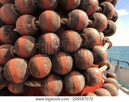 Wooden Parrel Beads wrapped around a red mast on a gaff rigged ketch sailing boat with a blurred sea and sky background selective focus with space for text.
