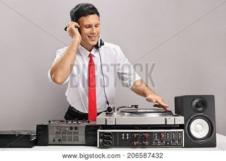 Formally dressed guy playing music on a turntable isolated on gray background