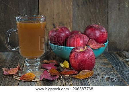 hot apple cider with autumn leaves and red apples in turquoise bowl