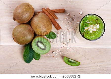A view from above on a pile of whole and cut in half kiwi fruits with decorative mint leaves and cinnamon spices. Creamy, thick kiwi smoothie on a light wooden table background.