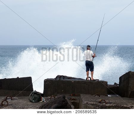 older man fishing in the sea stood on rocks with dramtic waves and surf breaking over the cliffs and blue sky