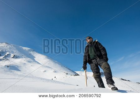 climber with an ice ax in the snowy mountains