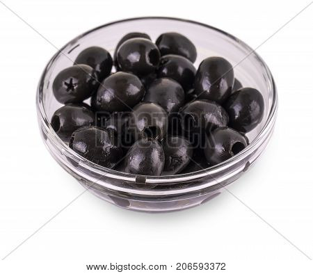 Black Olives without pits lie in a glass cup on the white background.