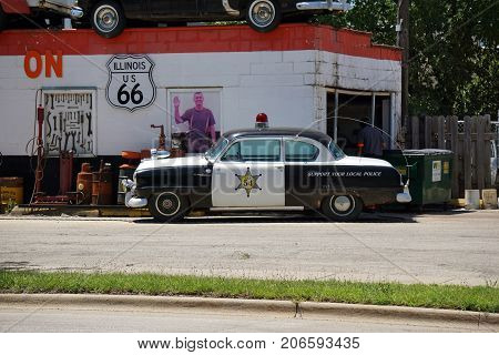 JOLIET, ILLINOIS / UNITED STATES - JULY 25, 2017: An antique black and white police car is parked outside Dick's Towing on US Route 66, a popular roadside tourist attraction on Broadway Street.