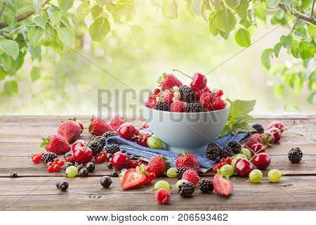 Ripe berries in a bowl on a wooden table on a background of green leaves