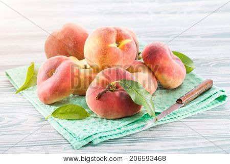 Ripe peaches with leaves on a green napkin on a wooden background