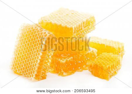 Pieces of honeycomb with honey on a white background