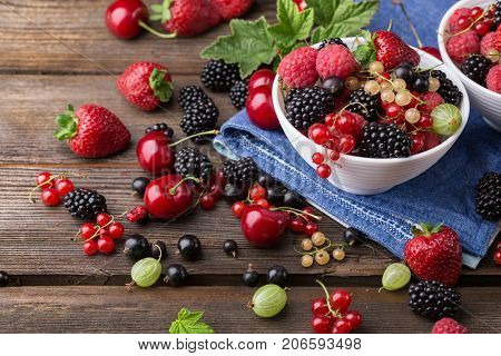Fresh ripe berries from a garden in a white bowl on a wooden table