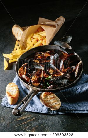Freshly cooked mussels in tomato sauce with toasts and French fries