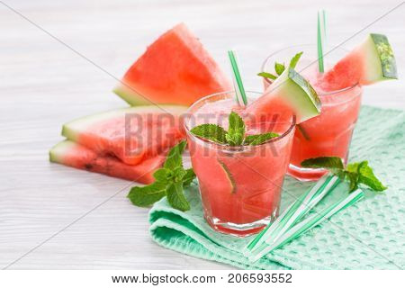 Two glasses with a refreshing drink from watermelon with lime and mint