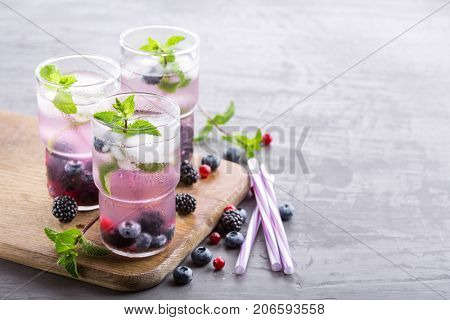 Refreshing summer berry drink with mint on a wooden board