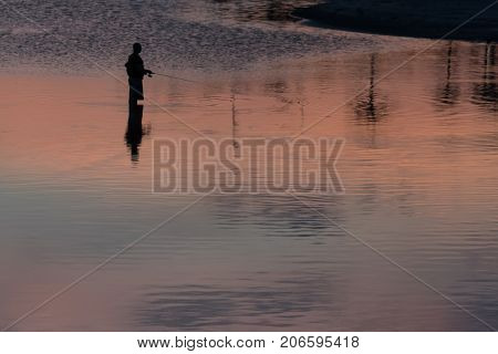 Silhouette of unrecognisable fisherman in the lake on sunset