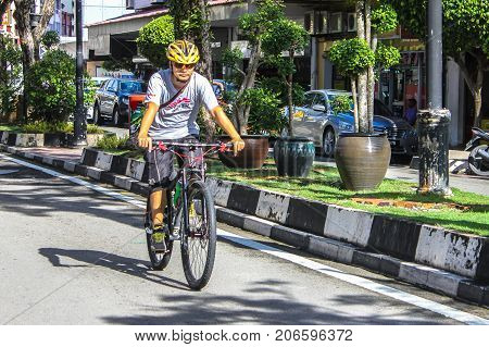 Labuan,Malaysia-Sep 30,,2017:Local man cycle towards Labuan street during the morning commute in Labuan,Malaysia.Malaysia is encouraging people to cycle for recreation & to commute to work.