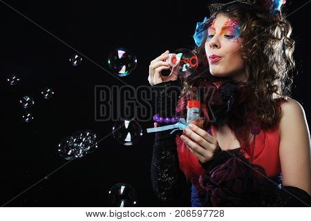 Fashion model with creative make-up blowing soap bubbles. Doll s