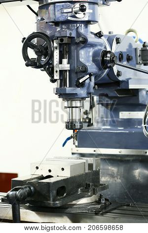 drill machine stand in garage or workshop. Machine controlled by automation and programmable. Technician use the machine for drilling the object or structure.