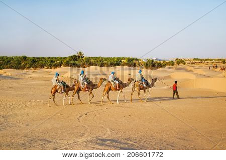 Tourists and bedouins on camels meet sunset in Sahara desert. Beautiful landscape with sand dunes and clear blue sky. Tunisia.
