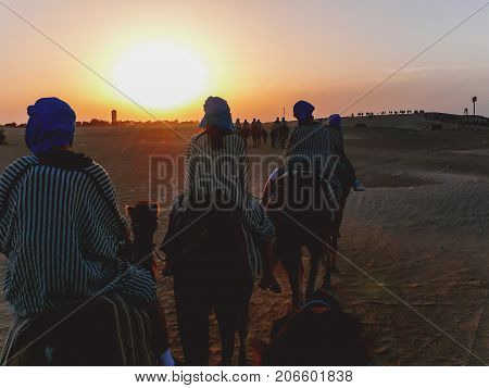 Tourists and bedouins on camels meet sunset in Sahara desert. Tunisia.