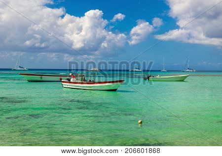 Wooden colorful boats on the azure clear water of the Caribbean Sea on a background of blue sky with white clouds, Dominican Republic, Caribbean Islands, Central America