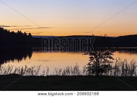 Sunset in the woodland, lake. Hills and ridges in the horizon, silhouette.