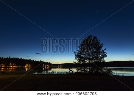 Sunset in the woodland, lake. Hills and ridges in the horizon, silhouette. Pathway along the lake.