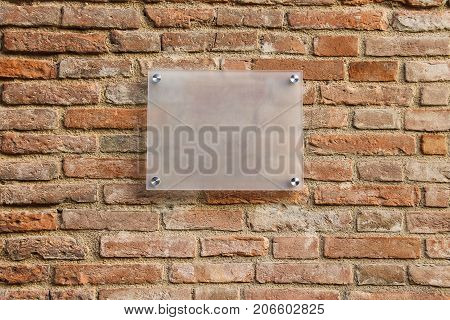 Empty information sign on old brick wall. Semitransparent milk color