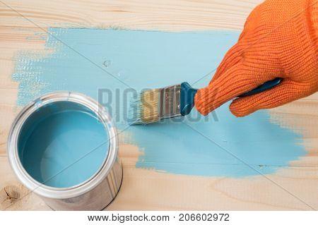 worker paints board blue paint. blue paint. worker paints board