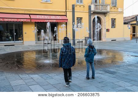 Vignola Italy - October 30 2016: Two boys looking at fountain in historic city centre. Emilia-Romagna Modena