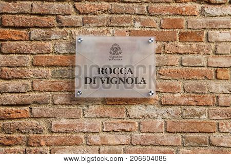 Vignola Italy - October 30 2016: Information sign on old brick wall of ancient fortress. Emilia-Romagna Modena