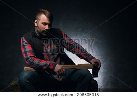 Dangerous-looking axeman. Lumberjack with weapon. Armed rural man with axe on dark background closeup, spooky atmosphere, danger concept