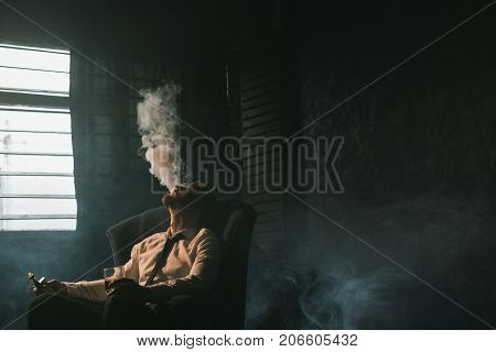 Businessman relaxing with vape and alcohol. Dark room with white atmospheric smoke background, rich people entertainment, private club for luxury life with free space