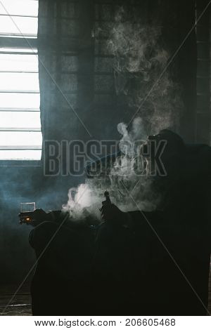 Male problems in life. Career crash. Successful man lost everything, despair in alcohol and vaping. Tired bankrupt, unrecognizable guy in smoke, dark room background, bankruptcy concept
