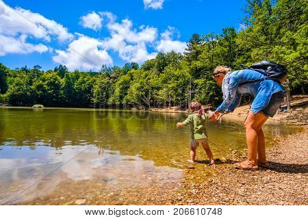 mother help baby to enter with feet in lake waters during a family trip in the nature of Foresta Umbra - Gargano Apulia - Italy