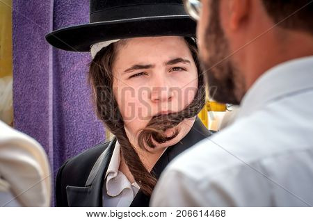 A young Hasid in a traditional Jewish hat and with long payos. Uman Ukraine - 21 September 2017: Rosh Hashanah Jewish New Year.