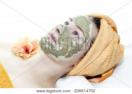 Girl with cosmetic mask of clay on her face close-up