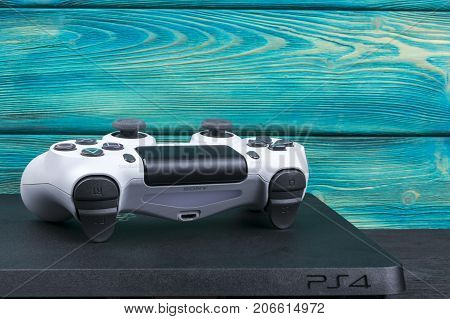 Sankt-Petersburg Russia September 24 2017: Sony PlayStation 4 Slim 1Tb and dualshock game controller on the blue wood background
