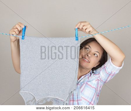 Smiling Attractive Woman Hanging Wet Clean Cloth To Dry On Clothes Line At Laundry Room on a grey background