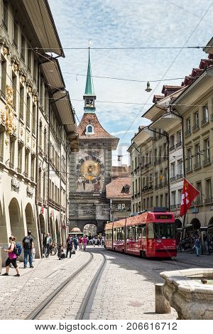 Bern Switzerland - May 26 2016: Street view on Kramgasse with red tram in the old town of Bern city. Kramgasse is a popular shopping street and medieval city centre of Bern Switzerland.
