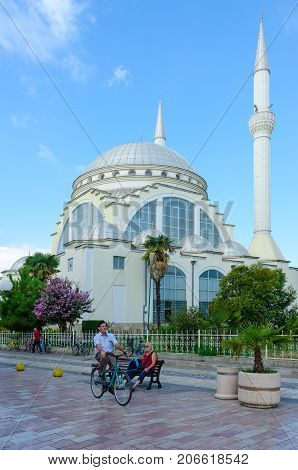 SHKODER ALBANIA - SEPTEMBER 6 2017: Abu Bekr Mosque or Great Mosque (Xhamia e Madhe). Unknown people ride bicycles and walk down pedestrian street (Rruga Kole Idromeno) in center of town of Shkoder