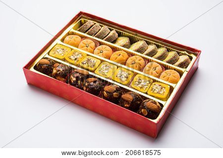stock photo of Indian sweet or mithai and oil lamp or diya with gift box and flowers on decorative or colourful background, selective focus