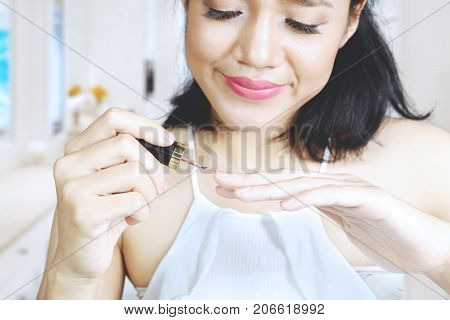Beauty concept. Pretty woman applying nail polish on her fingernail while sitting in the living room