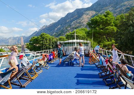 KOTOR MONTENEGRO - SEPTEMBER 10 2017: Unknown tourists are on upper deck of pleasure ship before setting off on tour of Bay of Kotor Kotor Montenegro