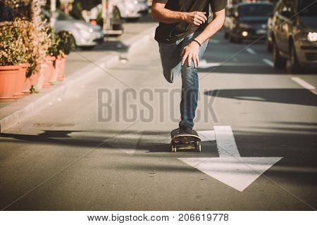 Pro skate rider ride skateboard in front of the car on the city road street through traffic jams