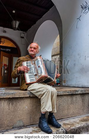 KRAKOW, POLAND - JUNE, 2012: Close up old man with accordion playing in the street