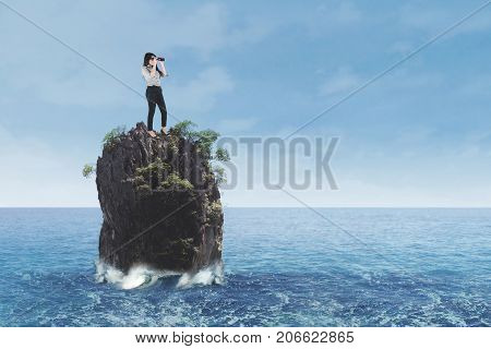 Young businesswoman standing on coral reef at sea while looking through binoculars