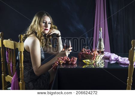 Busty young girl sitting at the table and holding a glass of wine on a black background