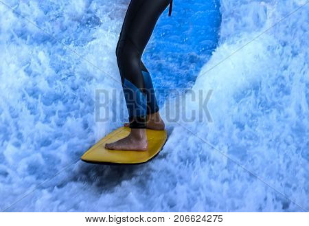 Windsurfer's legs closeup on a yellow surfboard against a background of blue bubbling water and white foam.