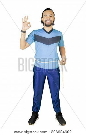 African man measuring his waistline with measure tape and showing OK sign in the studio