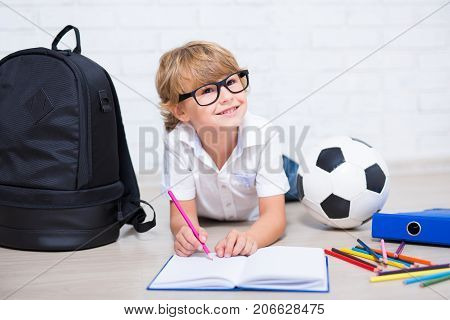 Little Boy In Glasses Doing Homework And Thinking About Something