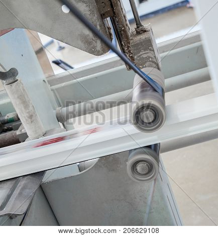 the machine glues the ribbon with the print on the profile. workshop for the production of PVC profile